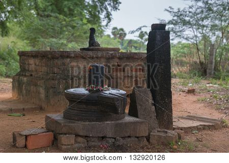 Chettinad India - October 17 2013: Closeup of black Shivalingam standing in vulva in a forest shrine near Kothamangalam. Altar to slaughter and offer animals in background under green trees.