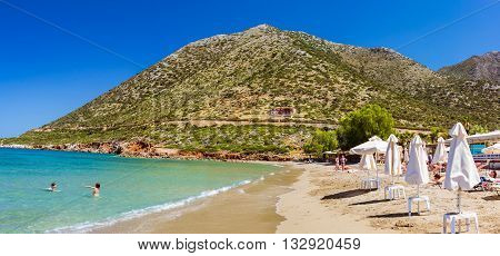 BALI GREECE - APRIL 28 2016: Sunny sandy Livadi beach in sea Bay of resort village Bali. Views of mountain shore washed by waves and sun loungers with parasols where sunbathing tourists. Bali Rethymno Crete Greece
