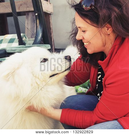 Happy Young Woman With White Fluffy Samoyed Dog