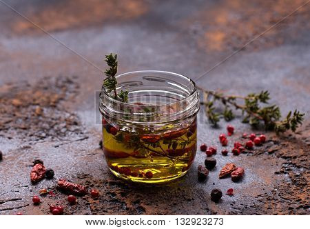 olive oil flavored with spices on dark background.