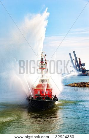 Fire fighting boat sprays water in port.