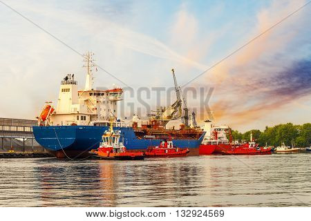 Tugboats maneuver a cargo ship in port of Gdansk Poland.