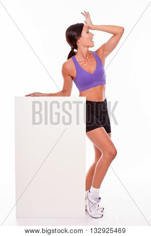 Healthy surprised brunette woman holding blank placard and looking away with her hand on her forehead while wearing violet and black gymnastic clothing isolated