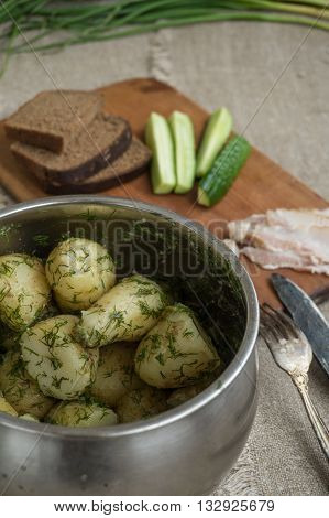 Boiled new potatoes with herbs in a pan. Lard, rye bread and cucumber are on a cutting board.