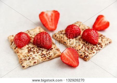 Red Fresh Strawberries are on the Cracker with Grains on the White Paper.Breakfast Organic Healthy Tasty Food.Cooking Vitamins Ingredients.Summer Fruits.