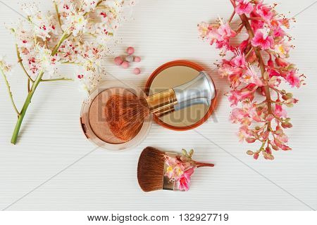 There White and Pink  Branches of Chestnut Tree,Bronze Powder with Mirror and Make Up Brushes are on White Table,Top View