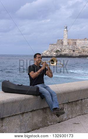 Havana, Cuba - January 20, 2016: A man playing the trumpet in the Malecon of Havana in Cuba