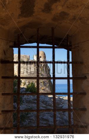 Bastion of venetian citadel Fortezza in Rethymno, Crete, seen through grated window