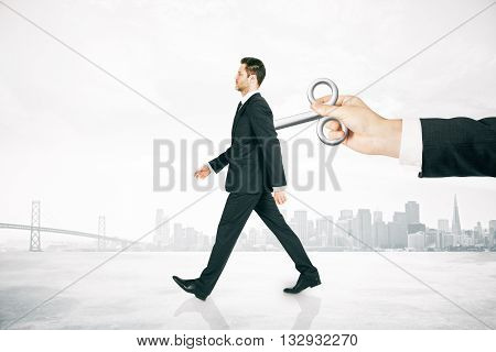 Hand activating walking businessman with a wind-up key on his back on foggy city background. Concept of control