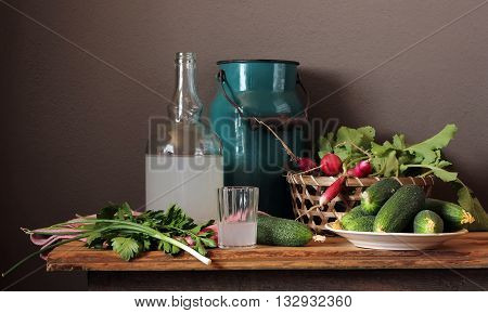 Still life with moonshine in the bottle radish and fresh cucumbers on the table.