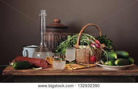 Still life with moonshine fresh vegetables in the basket and sausage in a rustic style.