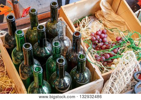Empty wine bottles in a wooden box and grapes