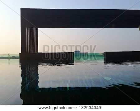 Swimming pool canopy and blue sky with reflection in water.