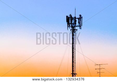Silhouette of cellular tower against blue pink and orange sunset sky. Also known as cell site or cell tower is where antennae and equipment are placed. Correct term is Base Transceiver Station.
