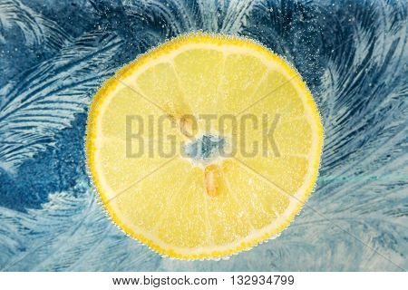 Slice of yellow lemon with seeds in water with bubbles on the background of a frosty pattern