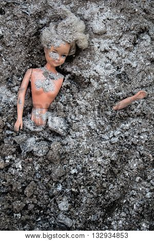 Girl doll toy lying in the pile of grey ash