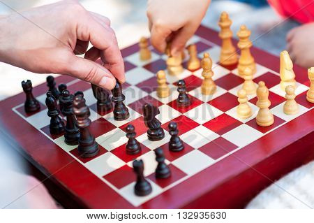 Close up of hands of old man and child playing chess on a board