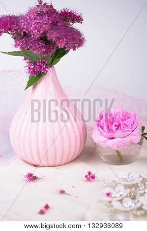 Pink flowers in a vase on wood background