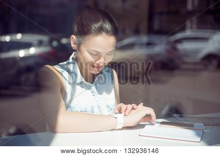 Due to  time. Glad and cheerful modern young woman checking time on her smart watch and using her cell phone while sitting near a window in a cafe and writing something in her copybook