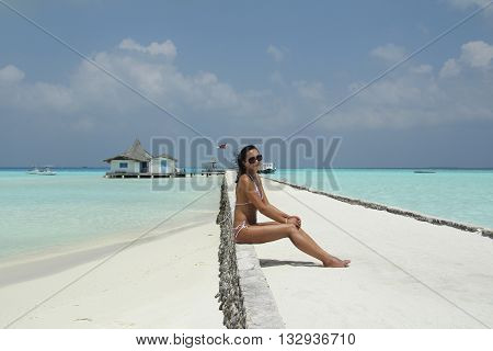 Tanned girl with dark hair is sitting in the beach