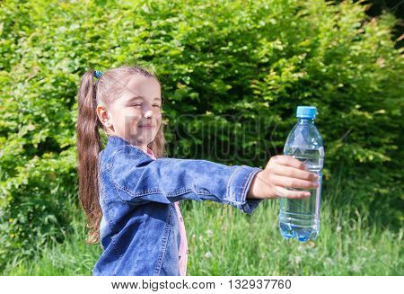 girl in a blue denim jacket giving a plastic bottle with water