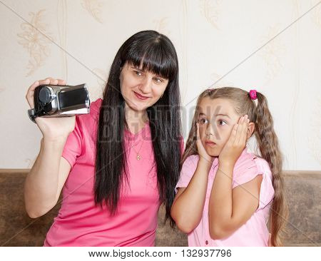 mom showing her little surprised daughter where babies come from on the display camcorder