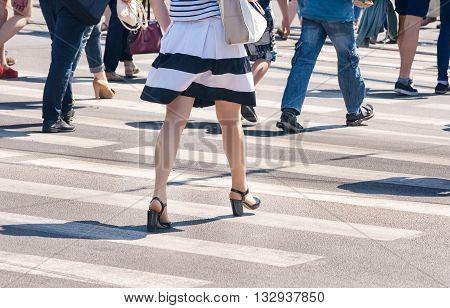 pedestrians walk on a crosswalk on sunny summer day