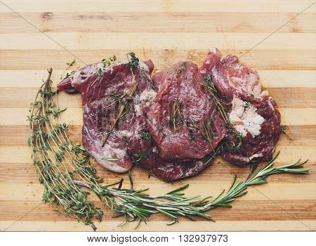 Fresh beef steak ready for BBQ cooking. Raw meat on a cutting board with rosemary leaf. Raw beef, veal meat on wood, closeup. Marinated in spices raw steak for barbecue. Top view