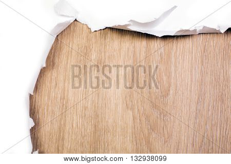 Closeup of ripped paper revealing wooden surface. Mock up