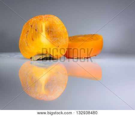 Two half of a persimmon on gray