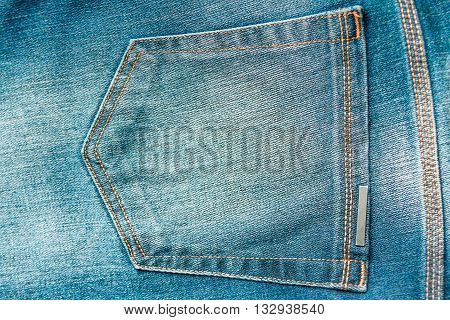 Back pocket of a blue jean with yellow stitching