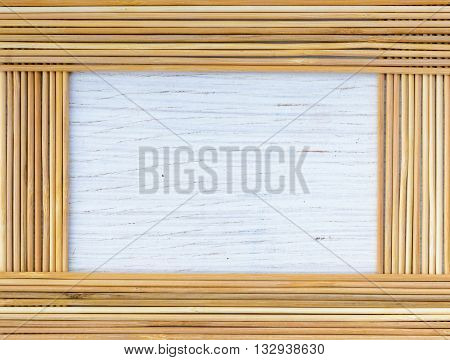 Frame from bamboo sticks on white wooden background