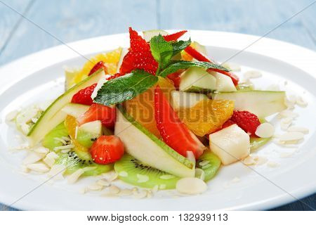 Vegan food. Fresh fruits. Fruit salad at white plate. Fruit salad closeup. Healthy diet food, natural organic vegan salad with pear, strawberry, orange and almond slices.