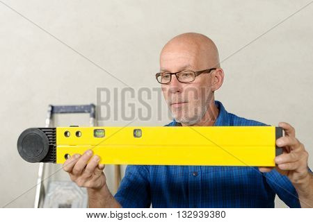 a mature man with a yellow spirit level