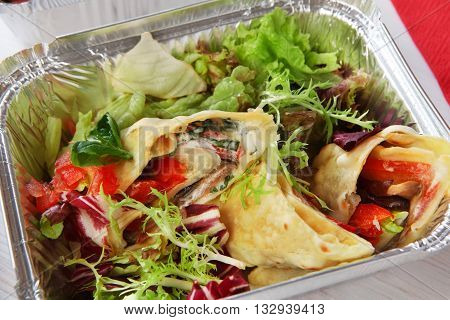 Healthy food in box. Natural organic food. Weight loss diet, low carb lunch take away in aluminium container. Healthy food background. Vegetable salad with crepe closeup at white wooden table