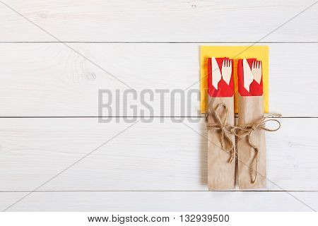 Copyspace at white wooden background for menu, plate or recipe. Food background. Fork and knife wrapped in brown paper, cutlery at wood top view with copy space. View from above