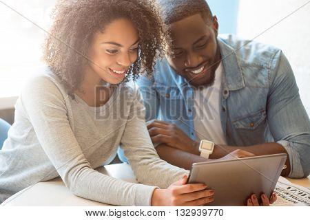 World of gadgets.  Smiling and positive modern young people sitting while using a digital tablet