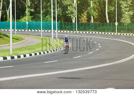 Cycling on the road. Woman cycling on countryside summer road or highway. Training for triathlon or cycling competition. Highway cycling