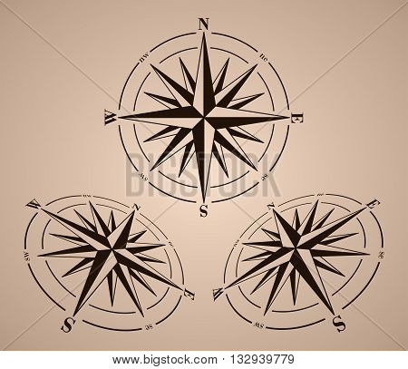 Compass roses set over brown background. Windroses set. Vector compass roses illustration.