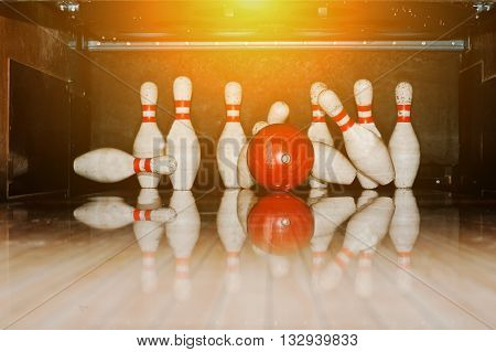 Ten White Pins In A Bowling Alley With Ball Hit
