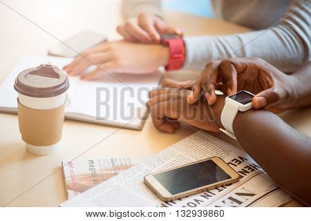 Time checking. Modern young people sitting in a cafe and drinking coffee while using their smart watches and phones
