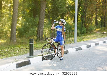 Female sportsman cyclist drinks water from the bottle at the race. Break, stop at road. Triathlon or cycling competition. Thirsty cyclist, rest at race