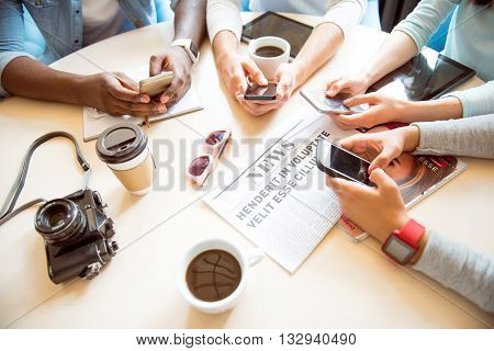Youth leisure. Close-up of group of modern young people holding mobile phones in their hands and typing messages while being in a cafe and drinking coffee