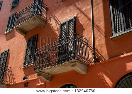 Traditional Italian balcony vykraski and terracotta walls. The windows shuttered the balcony casts a shadow.