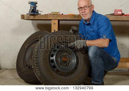 a mature man inflates a car tire
