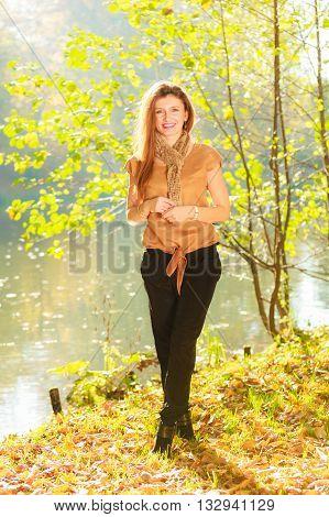 Girl taking walk near river. Autumnal nature fashion relax concept.