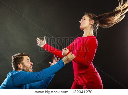Wife abusing husband. Aggresive woman beating slapping scared man. Couple in studio on black. Domestic violence aggression. Bad relationship.