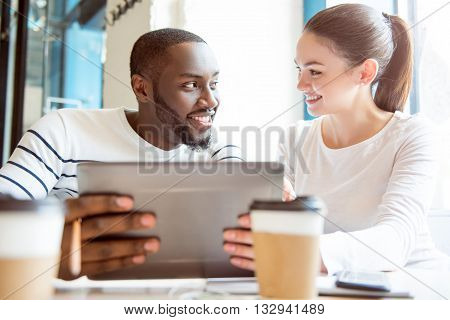 Listening to you. Cheerful and merry young people sitting together in a cafe and drinking coffee while holding and using a digital tablet