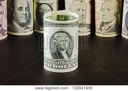 President with bills two dollars on a background of presidents from other denominations