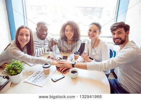 Being one united team. Smiling and positive young people sitting together in an informal atmosphere while drinking coffee and using various devices